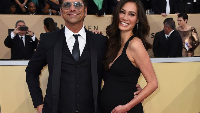 In this Jan. 21 photo, John Stamos, left, and Caitlin McHugh arrive at the 24th annual Screen Actors Guild Awards at the Shrine Auditorium & Expo Hall in Los Angeles.