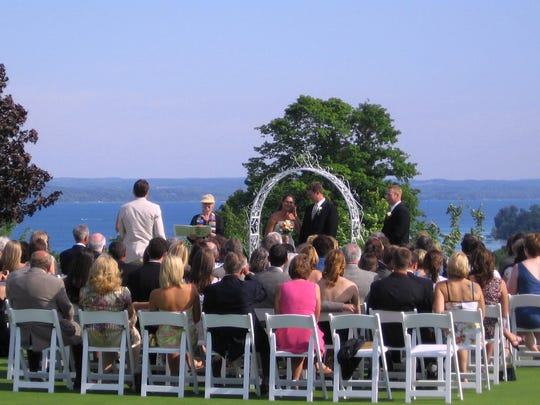 A wedding ceremony overlooking Torch Lake at A-Ga-Ming Golf Resort.