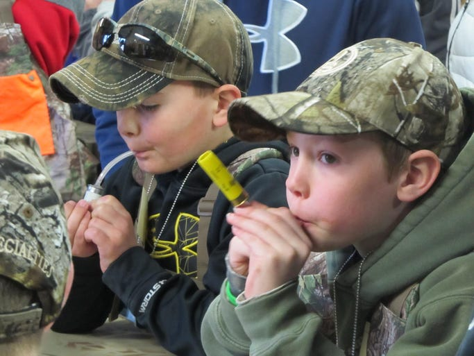 Hunter Marriott, right, of Calhoun, tests a call he madefrom a 20-gauge shotgun shell at the turkey clinic.