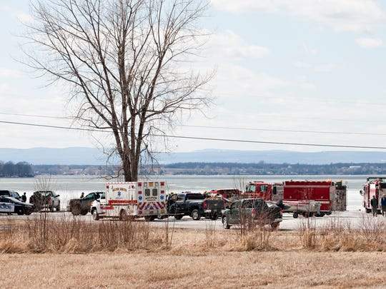 Emergency crews fill the Department of Fish and Wildlife's Van Everest fishing access in Milton after a plane landed on the ice on Lake Champlain on Saturday afternoon. The two people aboard were able to walk about three-quarters of a mile from the plane to shore and were reported to be uninjured.