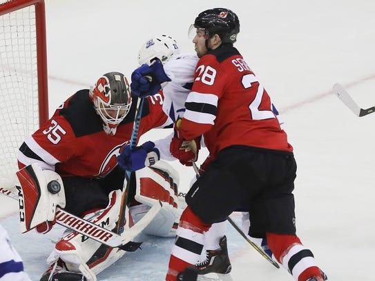 Devils goaltender Cory Schneider makes a save on Brayden