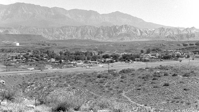 The then image, taken by Spectrum photographer Nancy Rhodes in June of 1988 shows a large empty patch of desert where the Red Cliffs Mall would be built less than a year later. Red Cliffs Drive is nonexistent in the then image and quite a few more homes can be seen in the Middleton and Green Valley areas north of the freeway in the now image taken by Spectrum photographer Jud Burkett. In the bottom right corner of the now image the Sterling Court Independent and Assisted Living Retirement Community can be seen as well.