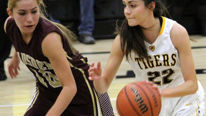 Carina Baca, right, drives up the court past Gadsden's Mileah Herrera on Tuesday night at the Tiger Pit.