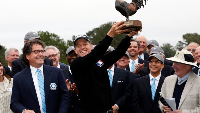 """Peter Malnati shows off """"Reveille,"""" the trophy of the Sanderson Farms Championship after winning for the first time on the PGA Tour, closing with a 5-under 67 to win in Jackson, Miss., Monday, Nov. 9, 2015. Malnati finished at 18 under in for the tournament. (AP Photo/Rogelio V. Solis)"""