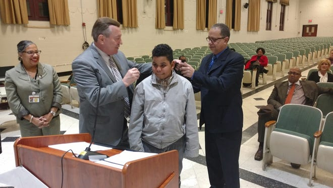 Principal Carlos Ortiz (in blue suit) and security director James Smith (in gray) put cape on the back of Paterson School 11 student Jose Santos for his heroic efforts when Ortiz suffered a heart attack at the school last month. Assistant Superintendent Sandra Diodonet looks on.