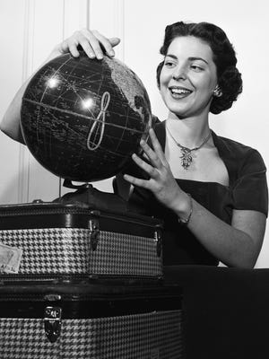 New Maid of Cotton Patricia Ann Mullarkey twirled a globe on Jan. 4, 1952, to search out points in Europe, South America and the United States that she will visit as cotton's goodwill ambassador in the coming year.