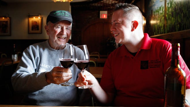 Joe Schuchter, director of marketing and sales of Valley Vineyards, clinks glasses with his grandfather, Ken Schuchter, founder of Valley Vineyards Thursday Feb. 18, 2016.