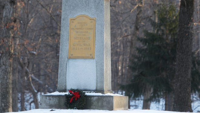 Volunteers braved the ice and cold Saturday to place wreaths at the headstones and monuments at the Indiana Veterans' Home cemetery in West Lafayette.