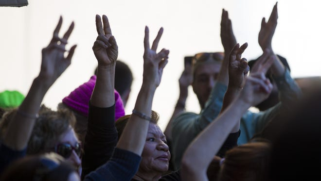 Protesters wave peace signs during a demonstration at Sky Harbor International Airport in Phoenix on Jan. 29, 2017. Protests have broken out at airports across the country in response to President Donald Trump's executive order, signed Friday, placing a temporary ban on entrance to the U.S. by people from seven Muslim-majority countries.