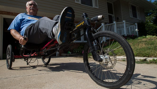 Steve Selzer, a founder of Sprint Selzer Bicycle Club, rides on a recumbent bicycle out of his garage on Monday, July 23, 2018, in Iowa City, Iowa.