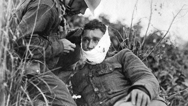 A wounded soldier from the 110th Infantry Regiment receives treatment on the battlefield at Varennes-en-Argonne, France on Sept. 26, 1918.