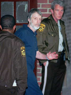 John du Pont waves as he is led into the holding area of the Delaware County Courthouse in Media, Pa., May 30, 1996.