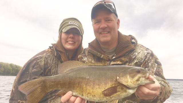 Mariah and Jeff Miller behind a big smallmouth bass on Chequamegon Bay.