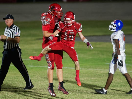 North Fort Myers High School's Blaise Sparks (74) and Clayton Savinsky (10) celebrate a touchdown scored by Savinsky against Cape Coral during second quarter play Friday at North Fort Myers High School. North beat Cape 41-0.