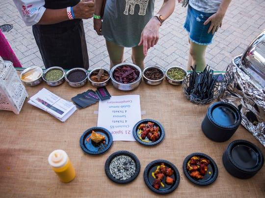 People decide which dish at the 21 Spices by Chef Asia booth they want to try during the 34th annual Taste of Collier at Bayfront Place on Sunday, May 6, 2018.