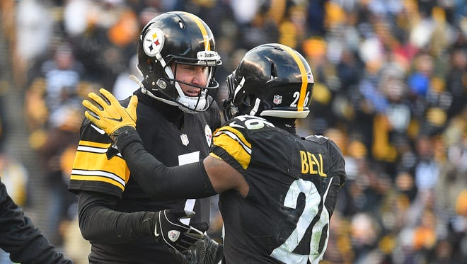 Pittsburgh Steelers quarterback Ben Roethlisberger (7) celebrates with Pittsburgh Steelers running back Le'Veon Bell (26) after a touchdown against the Miami Dolphins during the second half in the AFC Wild Card playoff football game at Heinz Field.