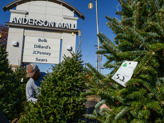Josh Black of JT's helps a customer with a Christmas tree in front of the Anderson Mall in Anderson on Monday.