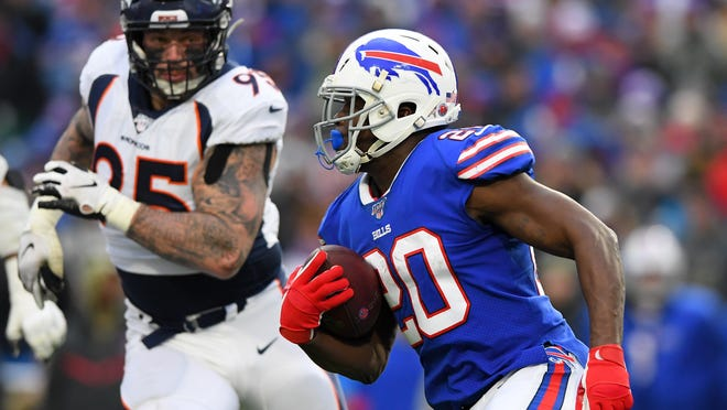 Bills running back Frank Gore carries the ball with Broncos defensive end Derek Wolfe in pursuit.