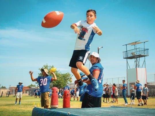 Jett Loe/Sun-News   11-year-old Steven Powers leaps to catch a football on Tuesday during the youth football camp hosted by Las Cruces High School.