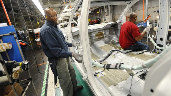 Nissan employee Cleotha Hill works on an Armada SUV as the vehicle passes his station on the assembly line at the company's manufacuring plant in Canton on Wednesday.