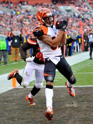 Cincinnati Bengals wide receiver Marvin Jones, left, catches a pass for a 21-yard touchdown as Cleveland Browns cornerback Charles Gaines (43) approaches in the second half of an NFL football game, Sunday, Dec. 6, 2015, in Cleveland.