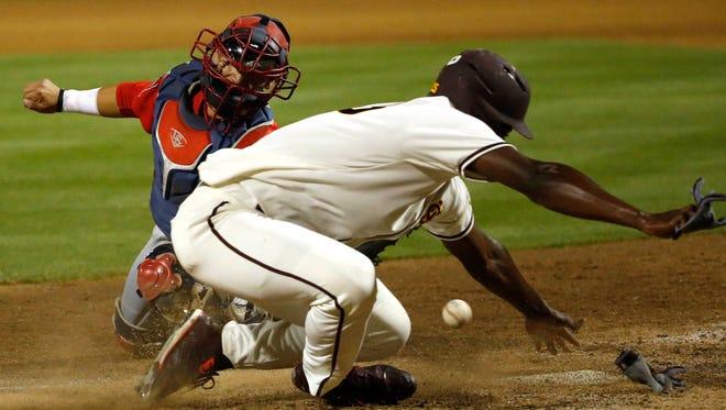 ASU baserunner Tyler Williams knocks the ball away from Arizona catcher Cesar Salazar to score during the fourth inning at Phoenix Municipal Stadium April 12, 2016.