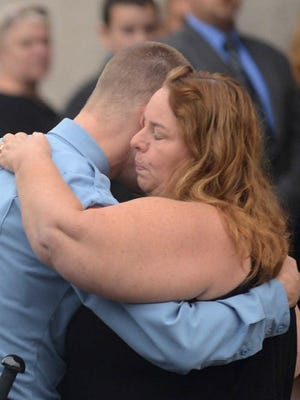 """In this Sept. 7, 2015 file photo, Melodie Gliniewicz, widow of Fox Lake police Lt. Charles Joseph Gliniewicz is embraced as she arrives for visitation of her husband in Antioch, Ill.   Authorities initially thought Gliniwicz had been killed in the line of duty, but investigators concluded Gliniewicz's death was a """"carefully staged suicide"""" by an officer who was on the cusp of being discovered for stealing from the village. A grand jury indicted Melodie Gliniewicz on Wednesday on felony counts of money laundering and disbursing charitable funds without authority for personal benefit."""