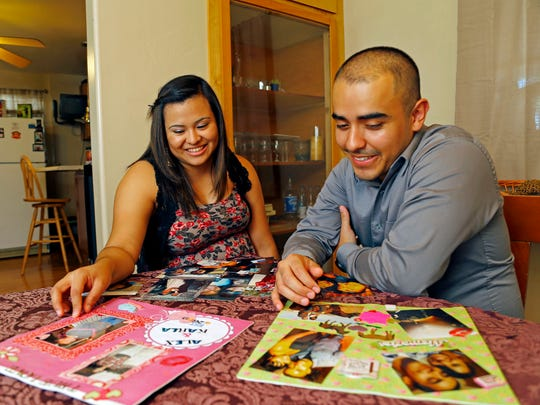 Karla Sanchez  and Alex Camarena reflect on when they first met while looking at photographs at Karla's home Wednesday, July 2,, 2014 in Phoenix, Ariz.  They were undocumented before applying for and receiving DACA in 2012, now they must renew their status. They've been together for almost 5 years, while DACA has given them a lot of opportunities, they live each day knowing the status is only temporary and in some ways this has impeded their plans for the future.