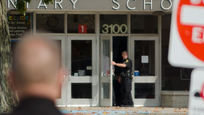 Law enforcement works at the scene of a bomb threat at Sutton Elementary School in Muncie on Friday, Oct. 23, 2015.