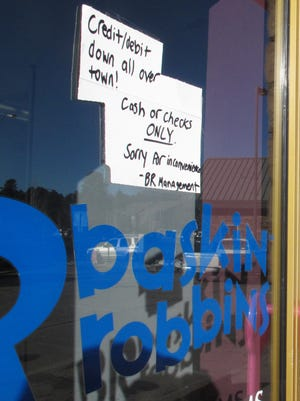 A sign posted outside a Baskin-Robbins ice cream store in Flagstaff, Ariz. advises customers that only cash or checks will be accepted due to an Internet and phone outage.