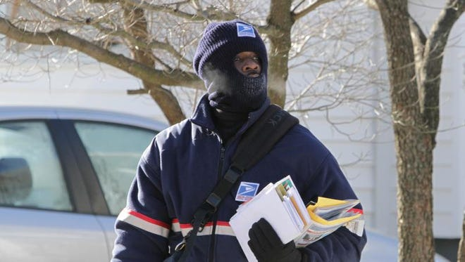 Peekskill letter carrier Bestman Ihim wears layers of insulated clothing while making door to door deliveries in Peekskill Jan. 7, 2014. While the temperature was in the single digits, the wind chill made the air feel well below zero.