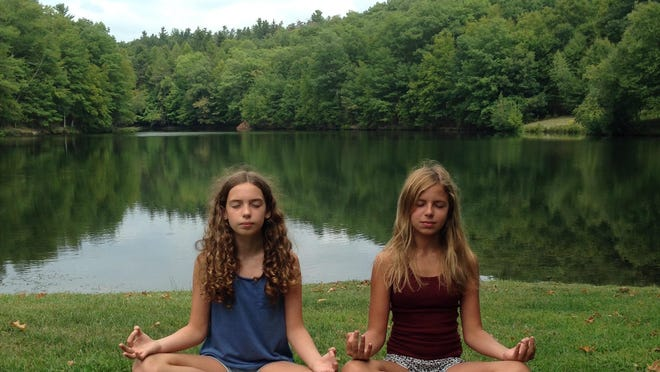 Lily, left, and Fiona practice a moment of mindfulness meditation.