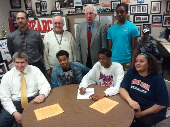 William Penn senior Derek Wilson signed his letter of intent Wednesday to play college basketball at Cecil College in Maryland. Seated, from left: Principal Randy James, brother Jahaire Wilson, Derek Wilson, mother Jenitza Barton-Mayo. Standing, from left: William Penn basketball coach Troy Sowers, athletic advisor John Moroney, athletic director Joe Chiodi, cousin Jeshaun Maddox. (SUBMITTED -- TROY SOWERS)