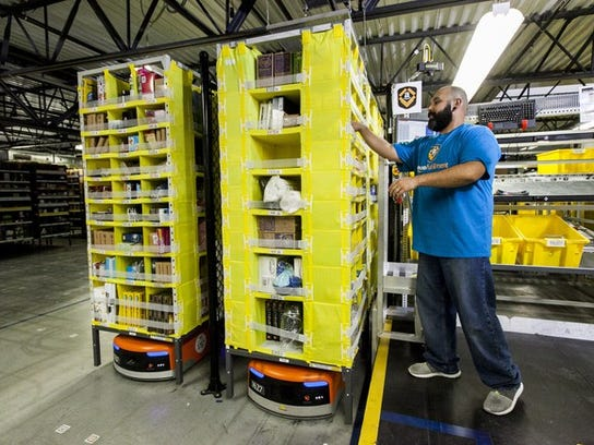 A worker and a robot in an Amazon warehouse