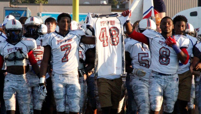 The Franklin Parish and Sterlington Panthers come out together carrying the jersey of Franklin Parish fallen teammate Tyrell Cameron before the Patriots' game against the Wossman Wildcats earlier this season. Cameron died in a game between Franklin Parish and Sterlington.