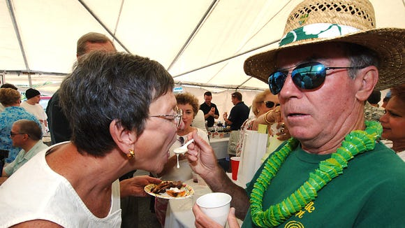 Ed McCaffrey gives Susanne McGrogan a taste of cream of crab soup from the Fenwick Crabhouse during 2015 Crab Soup Cook-Off.