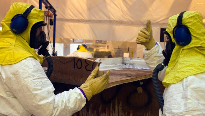 Crews repackage waste from a fiberglass reinforced plywood box into a container that can be shipped to the Waste Isolation Pilot Plant near Carlsbad, N.M.
