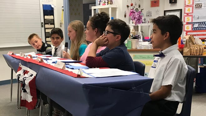 """Fifth-graders Blake W. (from left), Ben W., Ari E. (with the microphone), Bailee C., Rafael R., and Joshua M. answer questions before a panel of judges at the """"We the People"""" simulated hearing at J. L. Bowler Elementary School in Bunkerville on May 11, 2018."""
