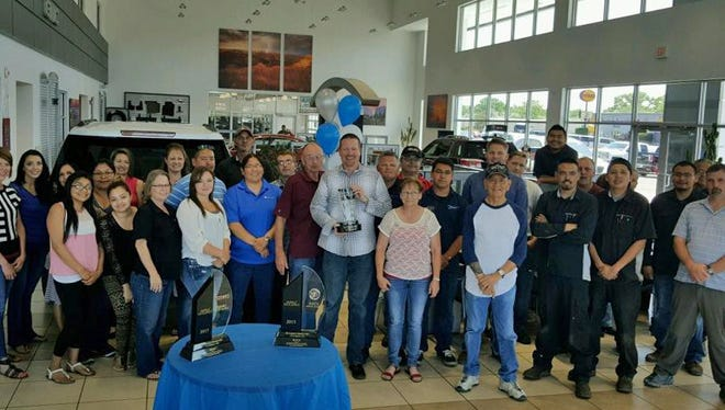 """The team at Hi-Country Buick GMC accepts the """"2015 Buick Dealer of the Year Award"""" at a celebration earlier this month at the Farmington car dealership. In addition to winning the award from General Motors for 2015, the Farmington dealership also earned the Buick Dealer of the Year award for 2014. To earn the award, a dealership must earn a score of 100 or higher on the Retail Sales Index. To earn the award this year, Hi-Country Buick scored 458 and had high marks in both customer service and customer retention."""