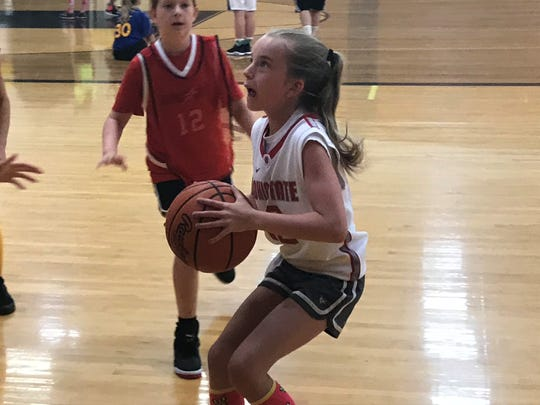 Fifth-grader Emily Tipton eyes the basket June 20 during Watkins Memorial's youth camp.