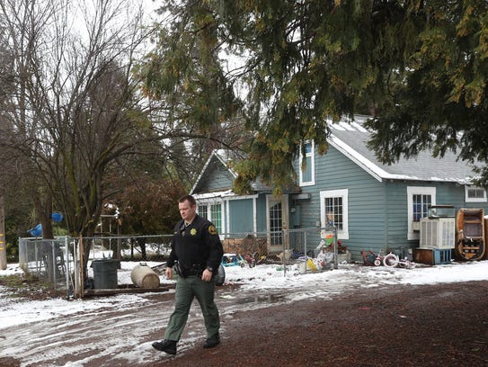 Shasta County sheriff's deputy Chris Wright leaves a house in Burney on Monday after interviewing someone there for a case. Wright is a deputy at the Burney substation and a resident of the town.