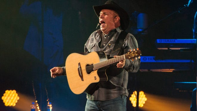 Country music star Garth Brooks, center wearing black cowboy hat, performs with band members kicking off his Garth Brooks World Tour at the Allstate Arena on Thursday, Sept. 4, 2014, in Rosemont, IL. (Photo by Barry Brecheisen/Invision/AP)