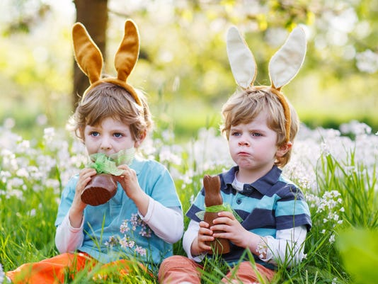 Two little children wearing Easter bunny ears and eating chocola