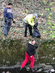 Lisa Snyder climbs down to collect debris out of the water at The Glen in Glen Ridge as David and JJ Snyder help out during a cleanup April 22, 2017.