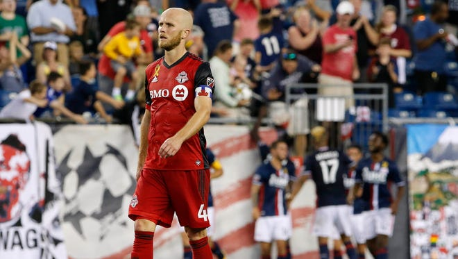 Toronto FC midfielder Michael Bradley walks back up field as the New England Revolution celebrate a goal during the second half of their 2-1 loss to the New England Revolution at Gillette Stadium.