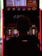 A woman gambles using a video slot machine at Belterra