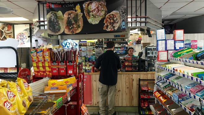 A customer orders tacos at the counter of Bunfire, a taco and gyro shop located inside an east Fort Myers gas station.