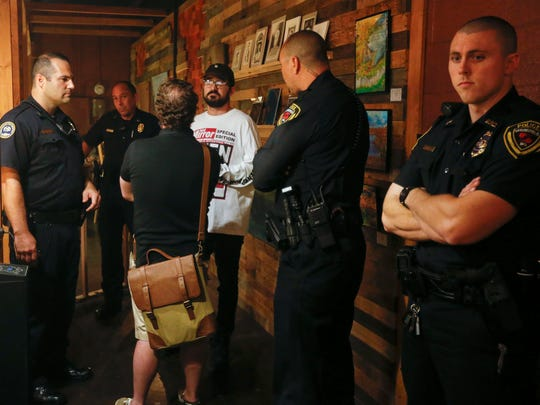 The fire marshal and Springfield police talk with Adam Rosenback, center left, primary tenant of Millet and Hammer, and concert promoter Johan Collins, center right, on Saturday, October 15, 2016.