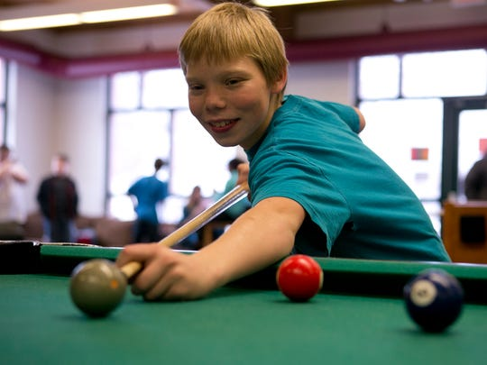 Dakota Klatt, 11, of Wisconsin Rapids plays pool in the Teen Center at the Boys & Girls Club of the Wisconsin Rapids Area at the Pitsch Center, Wednesday, Dec. 2, 2015. The club started offering a Diploma to Degrees program, designed to help teens to continue their educations after high school.