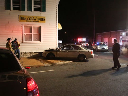 A car rests against a commercial building at the intersection of Newport Gap Pike and Old Capitol Trail after striking the building shortly before 11 pm Tuesday.